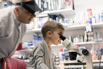 Little boy looking through microscope with help of his teacher.