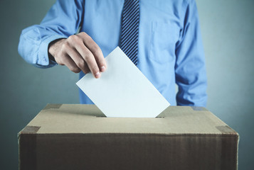 Man voting at the ballot box. Election and democracy concept