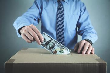 Man putting money on cardboard box. Save money