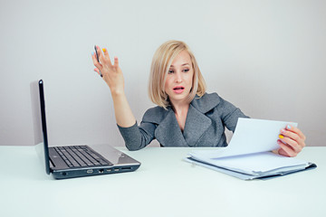 attractive smart blonde multitasking woman (business lady) in stylish business suit working with laptop and a bunch of folders angry and furious in panic in office . business concept and deadline