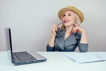 attractive woman blonde (business lady) in stylish business suit and a straw hat dreams about vacation and sunbathing in office with laptop on the table. travel concept and holiday