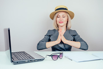 attractive smart multitasking female person (business lady) in stylish business suit and a straw hat meditatesin and dreams about vacation in office . travel concept and dismissal