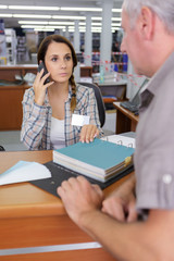 Woman on the telephone while in meeting with senior man