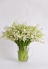 Foto op Canvas Bloemen bouquet lily-of-the-valley stands on isolated background in mug with water