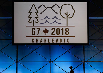 A Canadian mounted police officer walks past the Charevoix G7 logo at the main press center ahead of G7 Summit in Quebec