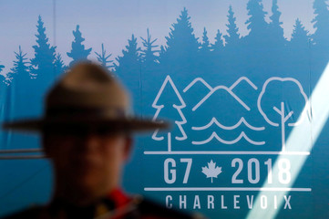 A Canadian mounted police officer stands next to the Charevoix G7 logo at the main press center ahead of G7 Summit in Quebec