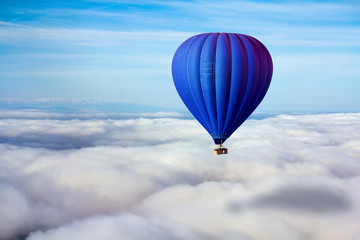 Foto auf AluDibond Ballon A lonely blue hot air balloon floats above the clouds. Concept leader, success, loneliness, victory