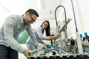 Young couple of students working at robotics lab