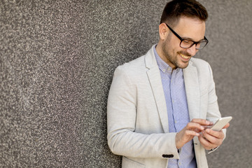 Young businessman in formal wear using mobile phone outdoor