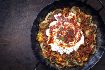 Traditional Turkey kolay yufka manti oven backed with lamb mincemeat as top view in a cast iron pan with copy space left