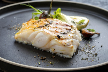 In de dag Vis Modern Thai fried cod fish filet with bok choi and mushrooms as close up on a plate
