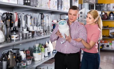 Young family couple is choosing blender for his kitchen in shop