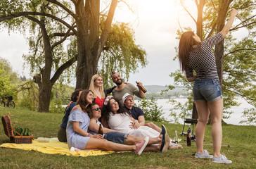 freunde machen ein gruppenfoto. brünette frau fotografiert ein selfie mit freunden. lifestyle picknick und grillen im park am see.
