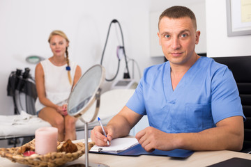 Doctor is writing the conclusion about result of examination of female client