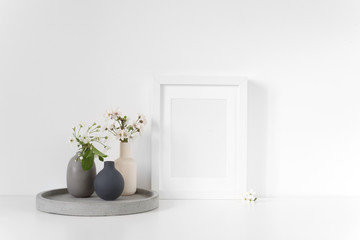 White frame mockup with spring cherry bouquet on concrete tray. Mock up for your photo, design or text.