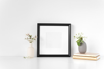 Black square frame mockup with spring flowers. Mock up for your photo, design or text.