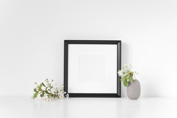 Black square frame mockup with spring cherry bouquet. Mock up for your photo, design or text. Background