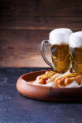 Photo of two glasses of beer and hot dogs on wooden tray