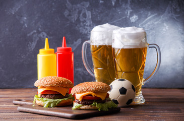 Image of two hamburgers, glasses, soccer ball, ketchup