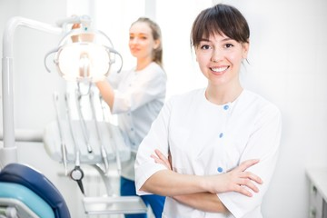 Girl Dentist Standing in the Office in the Foreground arms Crossed