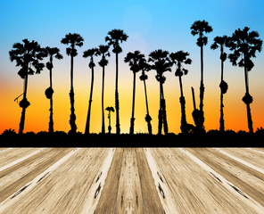 Empty top wooden table on silhouette palm tree on blurry sunset background