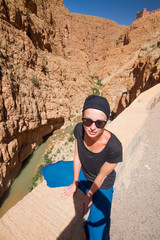 Female tourist relaxing on winding road bank in Dades Valley, Atlas mountains, Morocco.