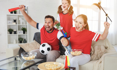family of fans watching a football match on TV at home.