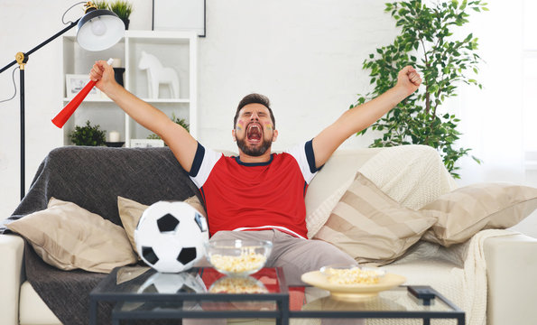 male soccer  fan watching a football match at home