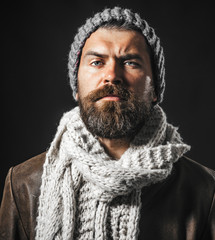 Casual attractive bearded male in leather jacket, white scarf and hat. Male fashion style. Bearded hipster wearing fashionable warm scarf and cap. Handsome man wearing demi-season clothing. Closeup.