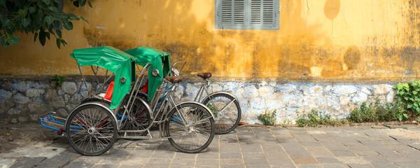 Vietnamese rickshaws (Cyclos) in Hoi An, Vietnam シクロとホイアンの黄色い壁