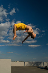 Tricking on street. Martial arts and parkour elements. Man flips back barefoot. Shooted from bottom foreshortening against sky.