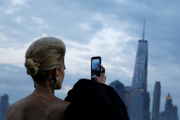 An attendee photographs the skyline of downtown Manhattan before the Saint Laurent Men's Spring/Summer 2019 collection presentation in Liberty State Park in New Jersey