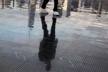 The skyline of downtown Manhattan is reflected in the runway as a security guard stands in place before the Saint Laurent Men's Spring/Summer 2019 collection presentation in in New Jersey