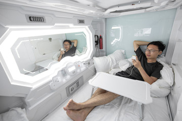 man using smartphone in the capsule hotel.