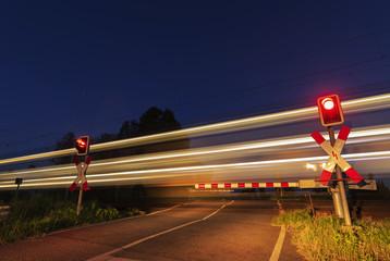 Langzeitbelichtung , Personenzug fährt Nachts an einer Schranke vorbei