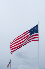 Two Unfurled American Flags Against a Cloudy Sky