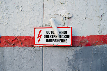 Caution. High voltage. Red warning sign on a metal door. In Russian