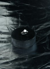 Engagement Ring on hockey puck with the inscription `Czech Republic` on the SILVER background.Black puck with Engagement Ring on SILVER background. Will you marry me?