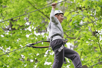 Young boy climbing trees at rope park