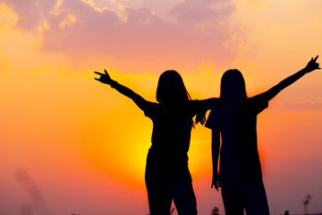 silhouette of two girls friend happy friendship smiling laughing with sunset view