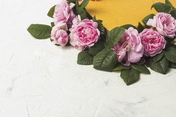 Pink roses and a book with a yellow cover on a light stone background. The concept of books about love and novels