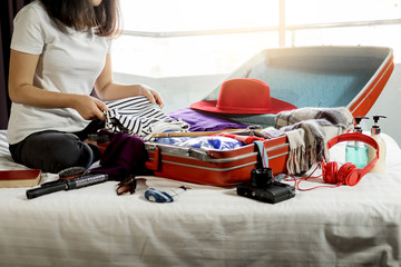 Woman hand packing a luggage for a new journey and travel for a long weekend.