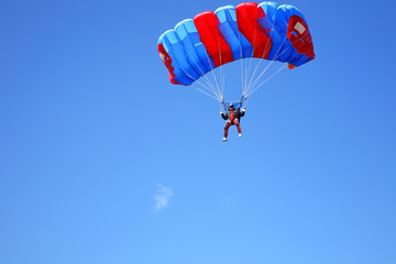 Paratrooper with open parachute against blue sky