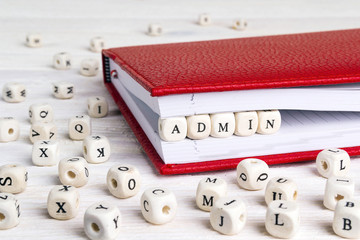 Word Admin written in wooden blocks in red notebook on white wooden table.