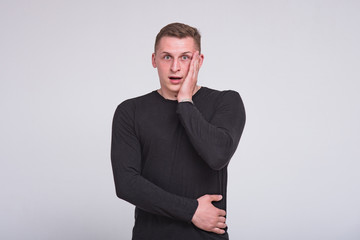 portrait of a cute young guy on a white background in different poses with different emotions.