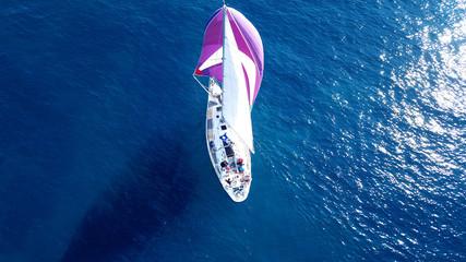 Aerial drone bird's eye view of beautiful purple sail boat cruising in deep blue ocean