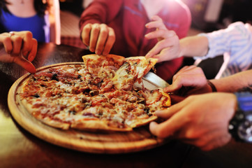 Hands taking pizza slices from wooden plate