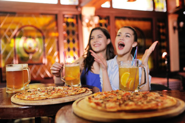 Tuinposter Pizzeria two young pretty girls eating pizza, drinking beer or a beer cocktail and watching football