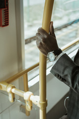 Cropped view of african american businessman wearing watch while taking train