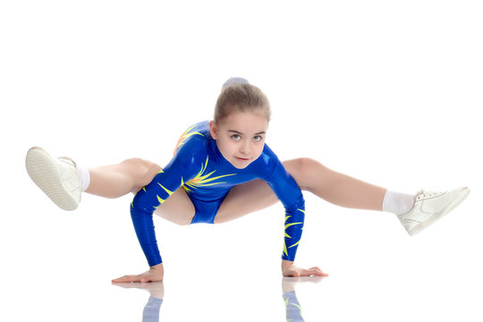 A girl gymnast performs exercises on the floor.